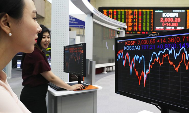 Employees of the Korea Exchange monitor the stock market at the Seoul office, Monday, the first day that extended trading hours took effect. Korea's bourse will open for 30 more minutes, a measure introduced to enliven the securities market and better compete with its Asian rivals. / Yonhap