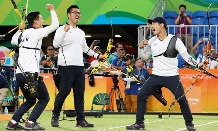 South Korean archers Ku Bon-chan, left, Kim Woo-jin, center, and Lee Seung-yun celebrate after winning gold in the men's archery team event at Sambodromo archery venue in Rio, Sunday (KST). / AP-Yonhap