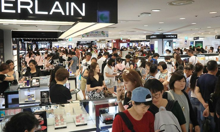 Chinese tourists crowd a duty-free shop in Lotte Department Store in downtown Seoul on Aug. 1. Market watchers worry that Korea's domestic demand will be hit by its plans to deploy a U.S. missile defense system on its soil, as China moves to impose economic sanctions against the country, hurting sales in the tourism and retail industries. / Yonhap