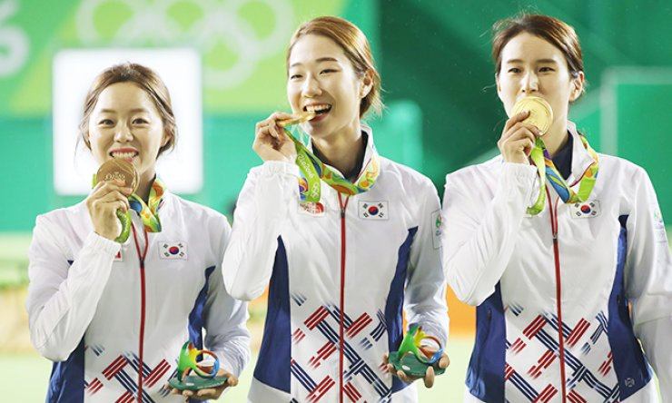South Korea's Chang Hye-jin, left, Choi Mi-sun, center and Ki Bo-bae bite their gold medals during the awards ceremony for the women's team archery event at the Sambodromo archery range in Rio, Monday (KST). / Yonhap
