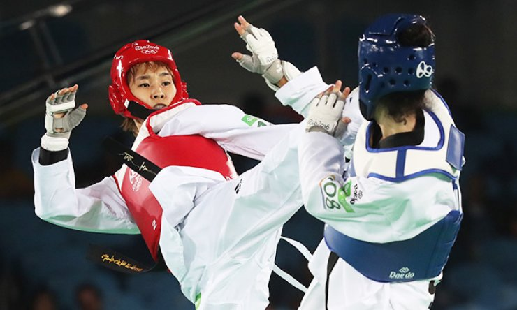 South Korea's Kim So-hui, left, lands a kick on Serbia's Tijana Bogdanovic in the women's 49 kg taekwondo gold medal bout at the 2016 Summer Olympics at Carioca Arena 3 in Rio, Wednesday. Kim clinched the gold after defeating Bogdanovic 7-6. / Yonhap