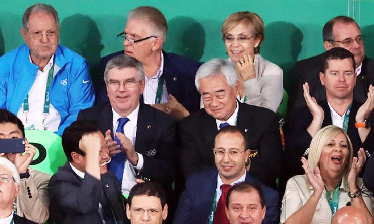 World Taekwondo Federation President Choue Chung-won, second row second from right, watches a taekwondo match along with International Olympic Committee President Thomas Bach, left of Choue, during the Rio de Janeiro Olympics at Carioca Arena 3, Aug. 17. / Yonhap
