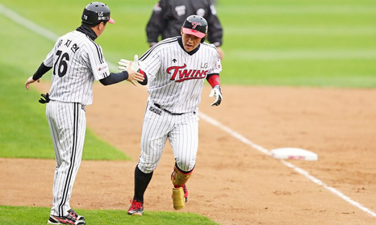 Yoo Kang-nam of the LG Twins, right, high-fives base coach Yoo Ji-hyeon after hitting a two-run homer during his team's first-round playoff game of the Korea Baseball Organization (KBO) at Jamsil Baseball Stadium in southeastern Seoul, Sunday. The Twins won 4-1 to take a 2-1 series lead. / Yonhap