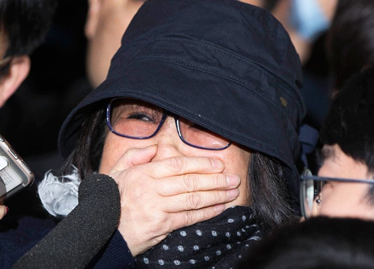Choi Soon-sil, the central figure in an influence-peddling scandal, covers her mouth with her hand, on the verge of crying, while surrounded by reporters and protesters before entering the Seoul Central District Prosecutors' Office for questioning, Monday. / Korea Times photo by Choi Won-suk