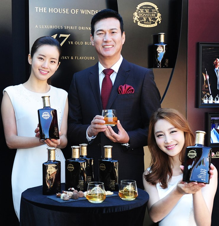 Diageo Korea CEO Cho Kil-soo, center, promotes W Signature by Windsor, the firm's latest premium spirit, at the former residence of the late President Yun Bo-seon in Seoul, Tuesday. The whisky is priced at 40,007 won, including value-added tax, for a 450-milliter bottle. / Courtesy of Diageo Korea