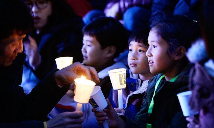 Children hold candles during a protest demanding President Park Geun-hye's resignation at Gwanghwamun in central Seoul, Saturday. / Korea Times photo by Shim Hyun-chul
