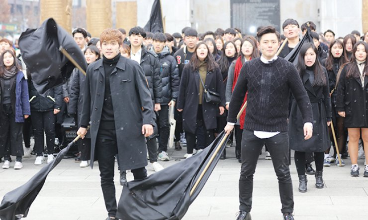 College students dressed in black call for the resignation of President Park Geun-hye, who allegedly helped her longtime friend Choi Soon-sil meddle in critical state affairs for her own benefit, at Gwanghwamun Square in central Seoul, Saturday. / Yonhap