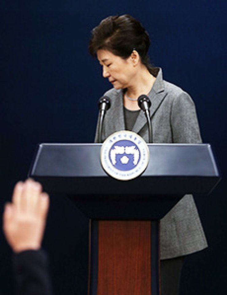 President Park Geun-hye leaves the briefing room at Cheong Wa Dae after delivering a speech about the influence-peddling scandal involving her aides, while a journalist raises a hand to ask the President to take questions, Tuesday. Park, as usual, refused to do so./ Korea Times photo by Koh Young-kwon