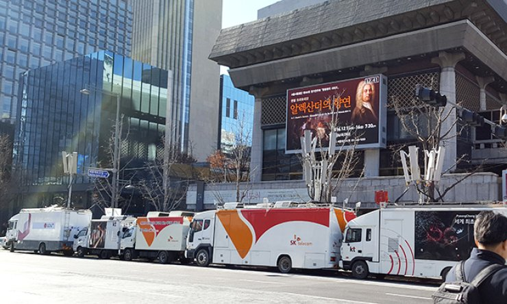 Mobile network company trucks are parked in front of the Sejong Center for the Performing Arts in central Seoul, Friday, working on the communication network system in preparation for the sixth weekly rally to be held Saturday. / Yonhap