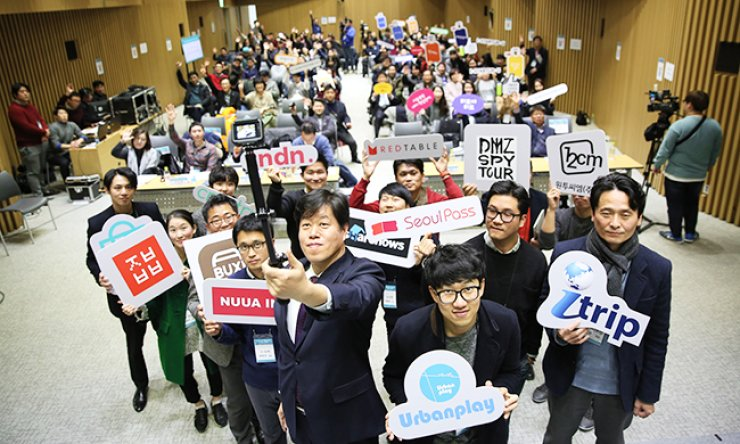 Kim Eui-seung, front row left, director general of the Seoul Metropolitan Government's tourism and sports bureau, holds a selfie stick to take a photo with representatives of 13 startups providing app-based tourism services, at City Hall, central Seoul, Tuesday. / Courtesy of Seoul Metropolitan Government
