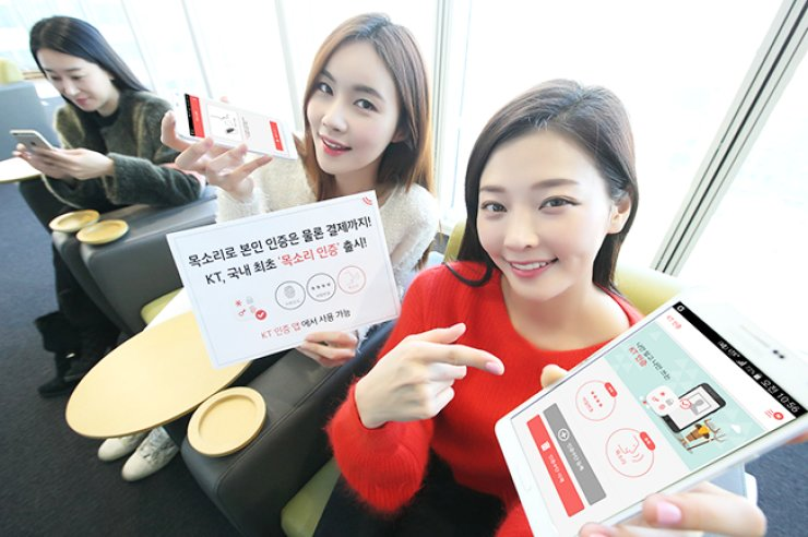 Models promote the voice recognition feature in KT's personal authentication mobile application at its headquarters near Gwanghwamun, central Seoul, Wednesday. / Courtesy of KT