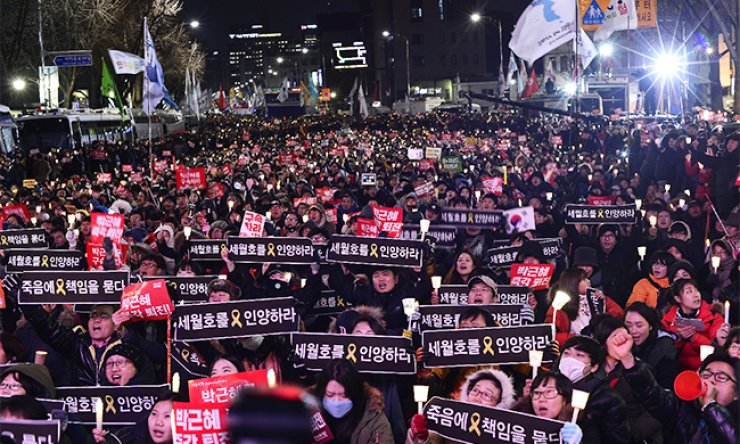 Citizens hold the seventh candlelit rally in Seochon, central Seoul, near Cheong Wa Dae, on Saturday demanding President Park Geun-hye step down immediately, the day after the National Assembly passed a motion to impeach her./ Korea Times photo by Shim Hyun-chul
