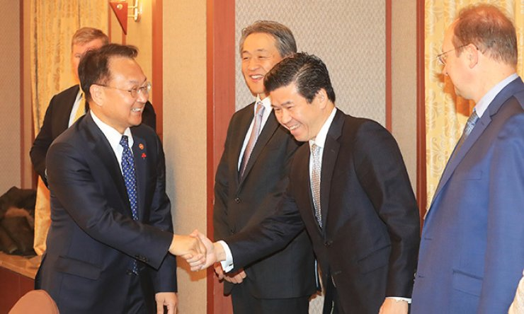 Finance Minister Yoo Il-ho, left, greets Chairman James Kim of the American Chamber of Commerce Korea, second from right, and other executives from foreign-invested companies ahead of a luncheon meeting in Seoul, Thursday. / Yonhap