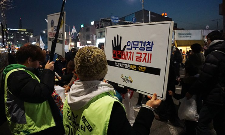 Activists hold posters questioning the constitutionality of police conscription, during a recent anti-Park Geun-hye protest in Seoul. / Courtesy of Center for Military Human Rights Korea