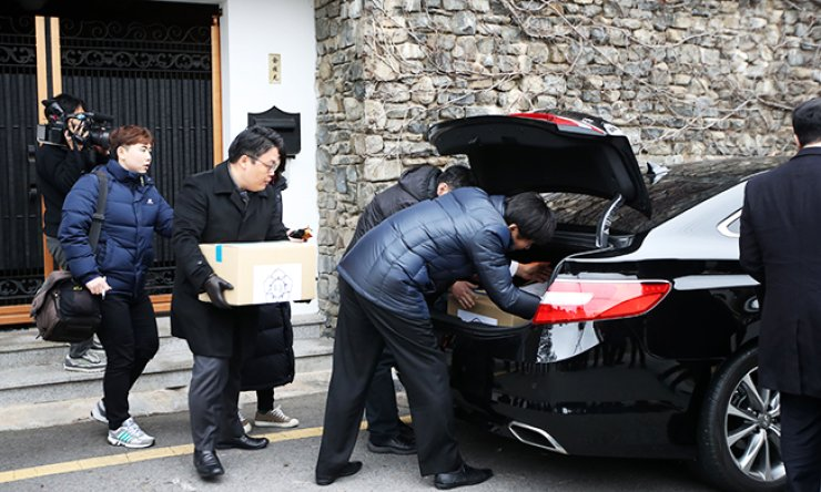 Investigators load boxes of evidence they secured during their raid of the home of former presidential chief of staff Kim Ki-choon in central Seoul into their cars, Monday, in their investigation into the corruption scandal involving President Park Geun-hye and her confidant Choi Soon-sil. / Yonhap