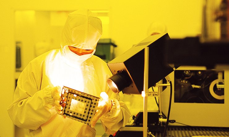A Samsung Electronics researcher takes a look at a semiconductor chip manufactured at the firm's factory in Hwasung, Gyeonggi Province. Analysts said Monday the firm's semiconductor division is expected to help underpin its profitability in the fourth quarter, backed by strong memory chip prices. / Korea Times file