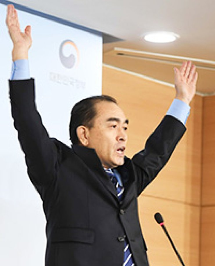Thae Yong-ho, the former North Korean deputy ambassador to the United Kingdom, raises his hands after speaking at a press conference at the government complex in downtown Seoul, Tuesday. He defected to the South in August./ Joint press corps