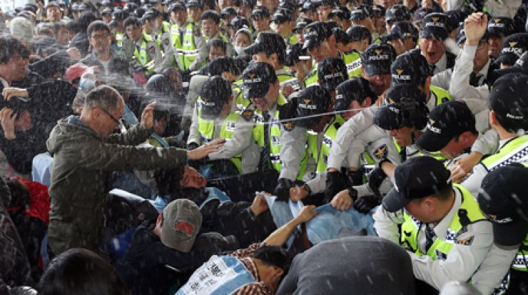 Police spray pepper spray at members of the Solidarity Against Disability Discrimination (SADD) at Seoul Express Bus Terminal, southern Seoul, on Disabled Persons' Day that fell on April 20. More than 300 disabled people gathered to demonstrate how difficult it is for them to simply get on a bus. / Yonhap
