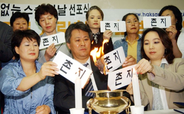 Members of Haksamo, a group of parents of schoolchildren, burn 'chonji' envelopes to advocate a chonji-free Teacher's Day, which falls on May 15, in Seoul in this 2004 file photo. Giving chonji, or small gifts, gift certificates or cash, to those in authority has been criticized as a practice that has gone from a gesture of gratitude to one that is nothing less than bribery. / Korea Times file