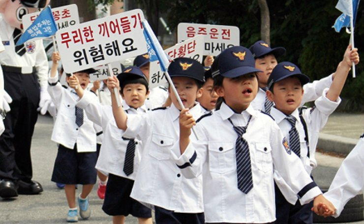 Children wearing police uniforms hold a campaign to ensure traffic safety in cooperation with police in Daejeon, Friday. / Yonhap