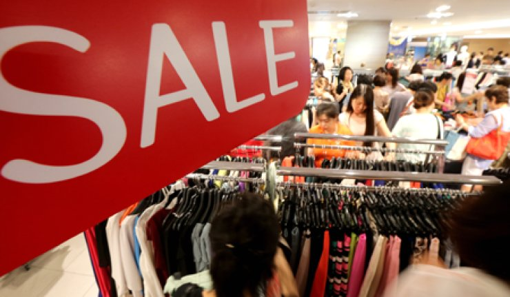 Customers crowd a department store in central Seoul, Sunday, to buy products at discounted prices. The store kicked off a summer bargain sale that will continue through July 31. / Yonhap