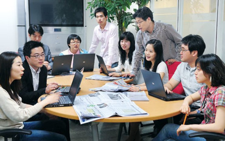 Interns hold a meeting to discuss their job training at a newspaper company in Seoul. Most interns expect to gain practical experience during their internship before embarking on their careers.                         /  Korea Times file