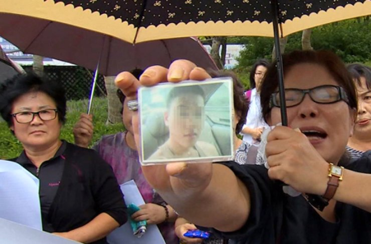 A weeping woman shows a picture of her late son at a press conference in front of the Ministry of National Defense building in Yongsan, Seoul, Aug. 6. She and other bereaved families called on the ministry to help restore the honor of soldiers who died from hazing while serving their mandatory military service. / Yonhap