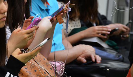 A smartphone user browses articles on social media. Some 74.3 percent of handsets used in Korea are estimated to be smartphones as of the end of2013, showing the highest penetration rate in the world. / Korea Times file