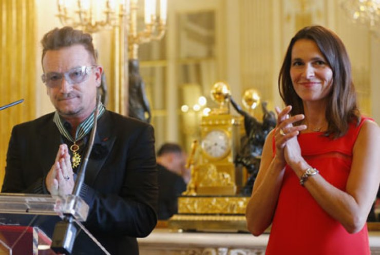Bono reacts with French Culture Minister Aurelie Filippetti, after he was awarded an 'Officier dans l'Ordre des Arts et Lettres' (Officer in the Order of Arts and Letters) at the Culture Ministry in Paris, Tuesday. / AP-Yonhap
