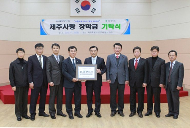 Kwang Dong Pharmaceutical Executive Director Lee In-jae, fourth from left, poses with Jeju Samdasoo Foundation President Oh Jae-yoon, center, at the Jeju Special Self-governing Province Development Corporation, Friday, after the pharmaceutical firm donated 200 million won in scholarship funds to the foundation as part of efforts to strengthen its cooperation with Jeju Island. Kwang Dong supplies bottled water Samdasoo in collaboration with the corporation./ Courtesy of Kwang Dong Pharmaceutical