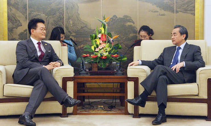 Chinese Foreign Minister Wang Yi, right, talks with Rep. Song Young-gil of the main opposition Democratic Party of Korea at the Ministry of Foreign Affairs in Beijing, Wednesday. Song led six other lawmakers to visit China for talks on the planned deployment of a Terminal High Altitude Area Defense (THAAD) battery here. / Yonhap
