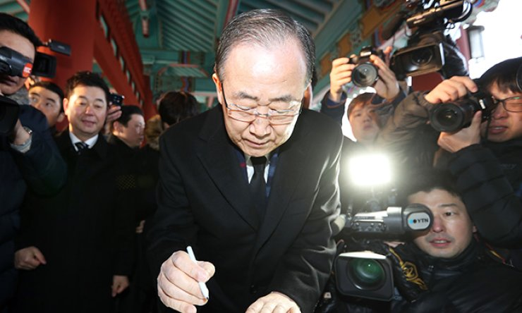 Former U.N. Secretary-General Ban Ki-moon writes in a guestbook during his visit to the May 18th National Cemetery in Gwangju, Wednesday, to honor those who were killed during a democratic uprising against military dictator Chun Doo-hwan, May 18, 1980. / Yonhap
