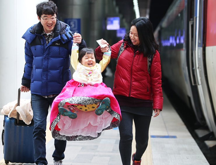 A child enjoys swinging from her parents' hands as they walk to board a train at Seoul Station, Thursday, to travel to their hometown for the Lunar New Year holiday. / Yonhap