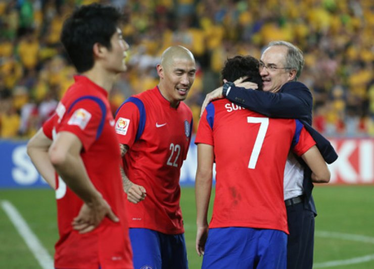 South Korea's coach Uli Stielike hugs Son Heung-min after a 1-2 loss to Australia in the Asian Cup final at Sydney Stadium, Australia, Saturday. / Yonhap