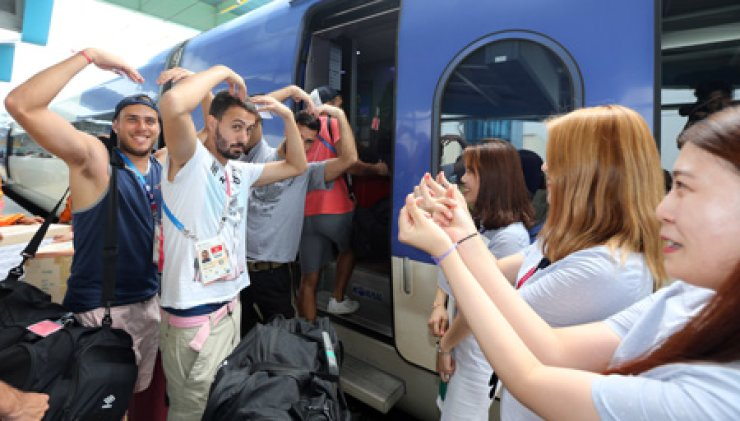 Athletes make a heart shape to volunteers at the Gwangju Universiade before getting on a train bound for Incheon International Airport. / Courtesy of GUOC