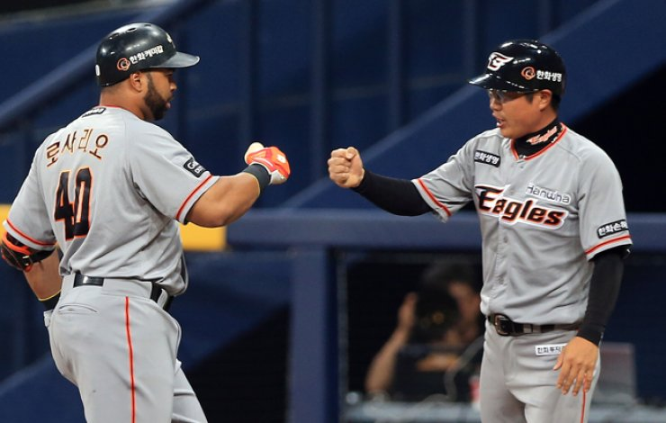 Wilin Rosario of the Hanwha Eagles, left, celebrates with a base-running coach after hitting an RBI single during his team's game against the Nexen Heroes at Gocheok Sky Dome in Seoul, Tuesday. / Yonhap