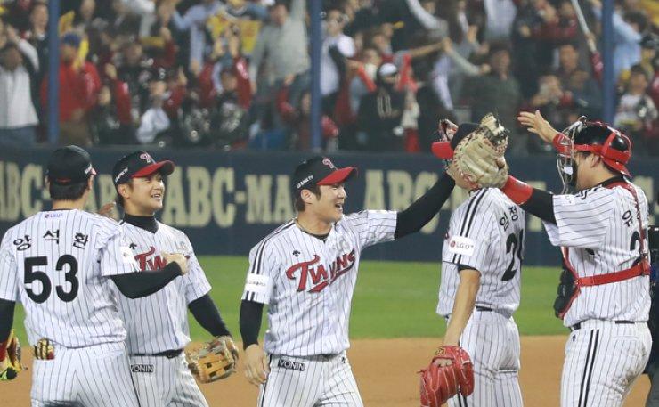 Oh Ji-hwan of the LG Twins, center, celebrates with his teammates after winning the Korea Baseball Organization postseason game against the Nexen Heroes at Jamsil Baseball Stadium in Seoul, Monday. / Yonhap