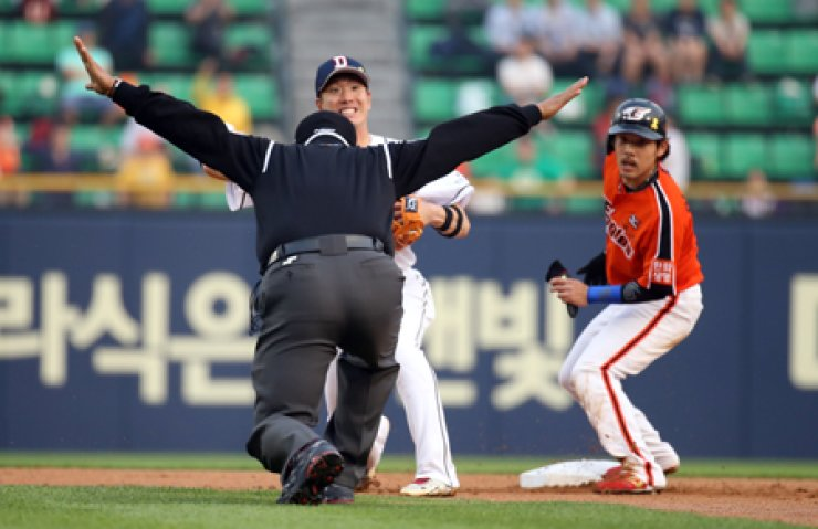 A second-base umpire calls Hanwha Eagles' Lee Yong-kyu, right, safe, as he reaches the second base in the first inning of the team's match against theDoosan Bears at Jamsil Baseball Stadium, Seoul, in this May 23 file photo.