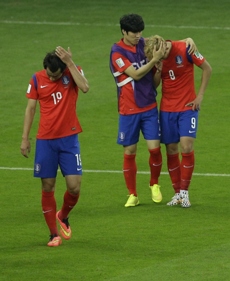 Korean players leave the pitch after their side lost 2-4 in a Group H match against Algeria at the Estadio Beira-Rio in Porto Alegre, Brazil, Sunday./ AP-Yonhap