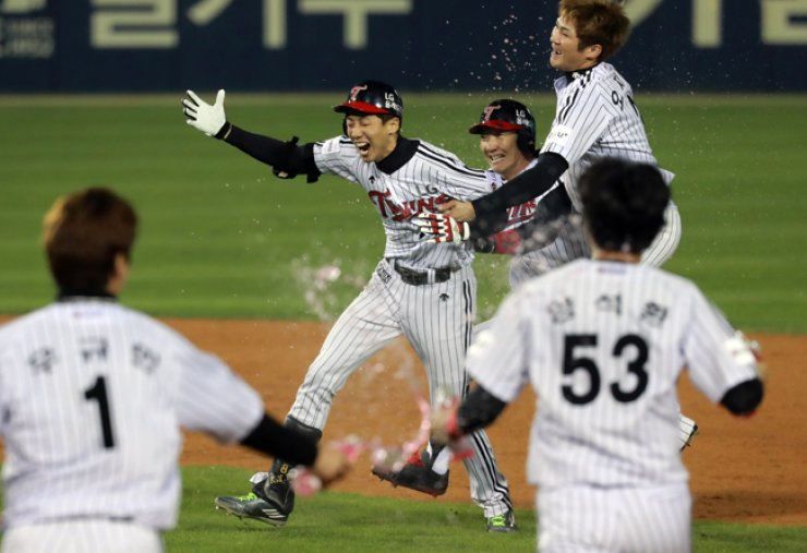 Kim Yong-eui of the LG Twins, center, celebrates with his teammates after hitting a sacrifice fly in the bottom of the ninth inning during the Korea Baseball Organization wild-card game between the Twins and the Kia Tigers at the Jamsil Baseball Stadium in southeastern Seoul, Tuesday. With his sacrifice fly, the Twins won 1-0 to advance to the playoff rounds.  / Yonhap