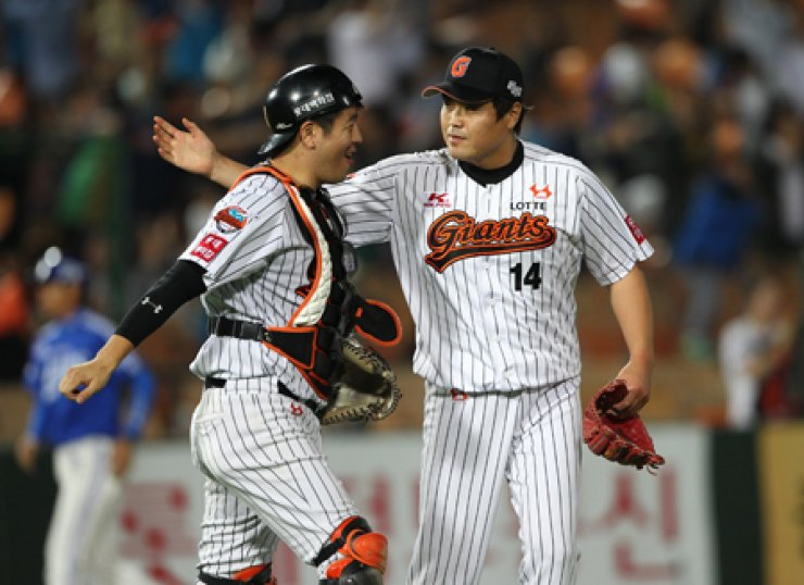 Lotte Giants pitcher Kang Young-sik, right, and catcher Kang Min-ho react after their team's 4-3 win against the Samsung Lions at Busan Sajik Baseball Stadium on Sept. 10. / Yonhap