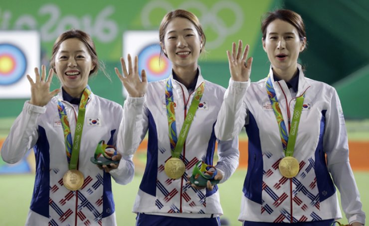South Korea's Chang Hye-jin, from left, Choi Mi-sun and Ki Bo-bae celebrate their gold medals during the awards ceremony of the women's team archery competition at the Sambodromo archery venue during the 2016 Summer Olympics in Rio de Janeiro, Monday (KST). / AP-Yonhap