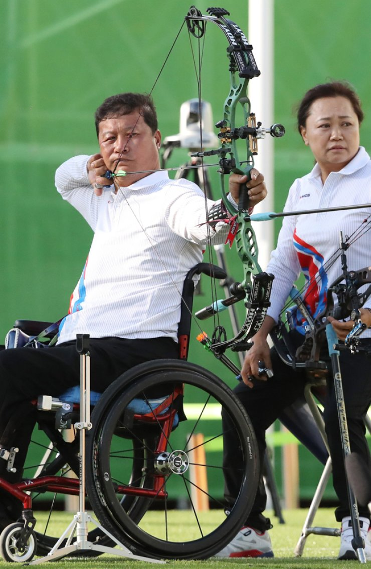 Acher Lee Ouk-soo, left, draws his bow in the bronze medal match of the Mixed Team Compound Open, at the Sambodromo venue in Rio de Janeiro, Brazil, Tuesday. Right is his teammate, Kim Mi-soon. / Yonhap