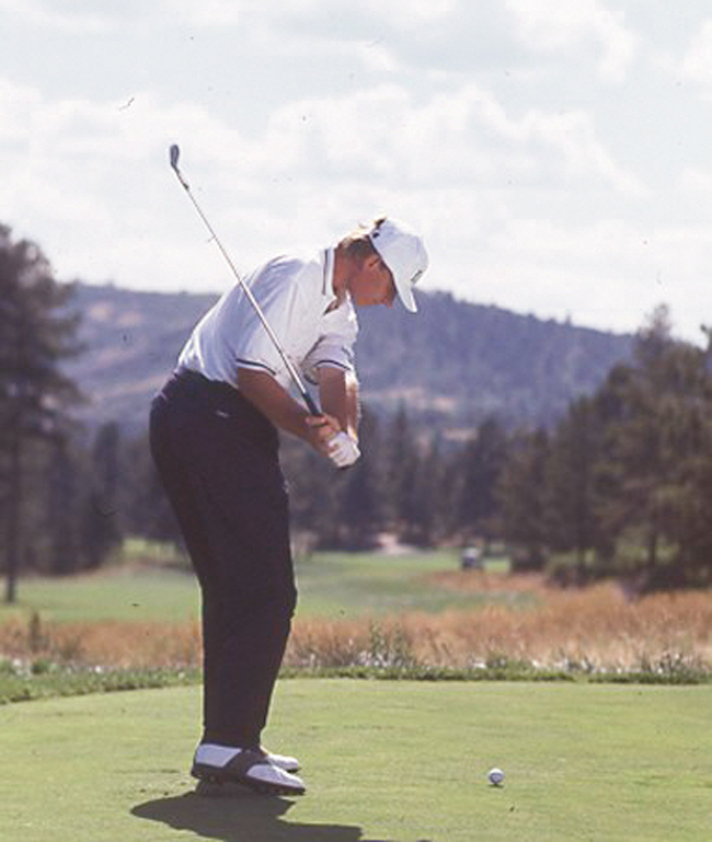 At the top of his swing, the palm of Ernie Els' right hand faces the sky, anchoring the club in the so-called 'tray' position. This is a very solid, no-nonsense position to begin his return swing to the ball. Because most of the work has been done in the backswing, the downswing appears to be quiet and fluid.As Els begins his downswing, three key moves occur simultaneously: (1) his left shoulder separates from his chin; (2) his hands separate from his right shoulder and (3) his left knee begins its drive to the target. This ensures that his hands have dropped straight down, with no tendency to throw the club over the top.'