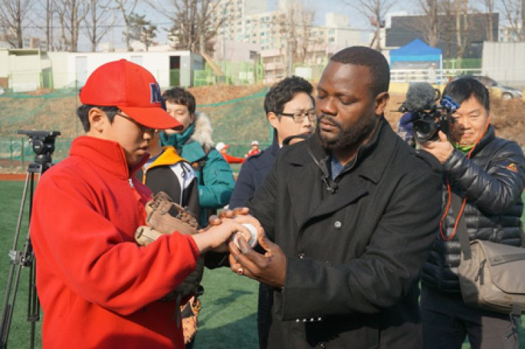 Fernando Rodney, right, a relief pitcher playing for Major League Baseball's Seattle Mariners, teaches a young player how to grip a changeup pitch atthe Songpa Little League Baseball Stadium in southern Seoul, Tuesday. / Korea Times photo by Baek Byung-yeul