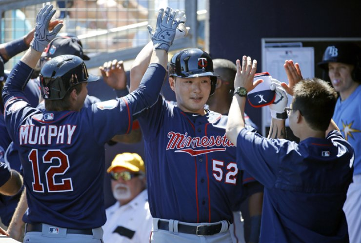 Minnesota Twins' Park Byung-ho, center, high-fives teammates in the dugout after hitting a grand slam in the first inning of a spring training baseball game against the Tampa Bay Rays in Port Charlotte, Fla., Sunday.  / AP-Yonhap