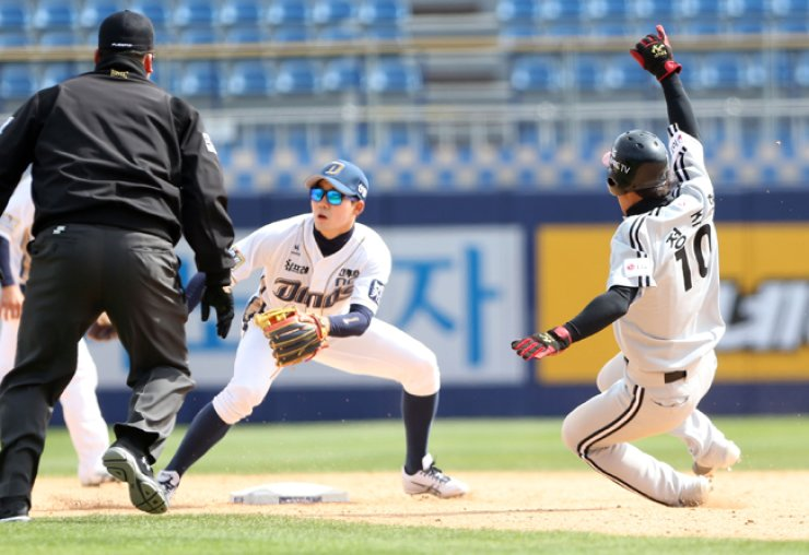 LG Twins' Jeong Ju-hyeon, right, slides into second for a stolen base under NC Dinos' shortstop Son Si-heon in the top of the third inning during their spring exhibition league match at Masan Baseball Stadium in Changwon, South Gyeongsang Province, Thursday. / Yonhap