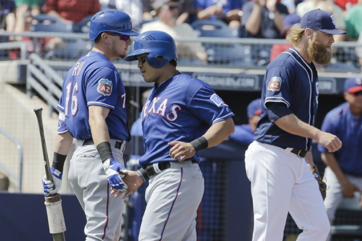 Texas Rangers' Choo Shin-soo, center, celebrates with teammate Ryan Rua, left, after scoring off a sacrifice-fly from Rougned Odor, not pictured, as San Diego Padres pitcher Andrew Cashner, right, walks back to the mound in the first inning of a spring training baseball game in Peoria, Ariz., Tuesday. / AP-Yonhap