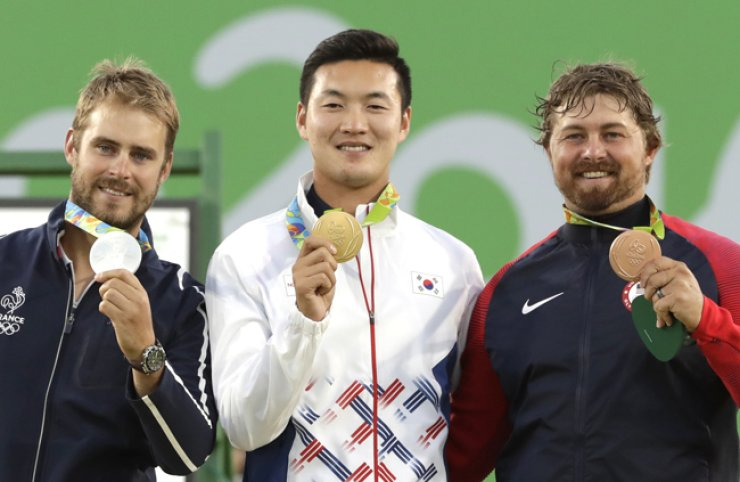 Gold medal winner Ku Bon-chan of South Korea, center, celebrates on the podium with silver medalist Jean Charles Valladont of France, left, and bronze medalist Brady Ellison of the United States at the awards ceremony of the men's individual archery competition at the Sambodromo archery venue during the Summer Olympics in Rio de Janeiro, Friday. / AP-Yonhap