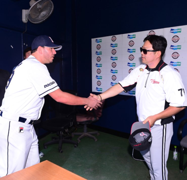 Doosan Bears pitcher Yunieski Maya, left, offers to shake hands with LG Twins manager Yang Sang-moon to apologize for his emotional outburst before a match at the Jamsil Stadium in Seoul, Sunday. Maya, who pitched for the Washington Nationals during his stint at the U.S. Major LeagueBaseball, flashed his finger toward the Twins's dugout, causing the two teams' players to clear the benches for an on-mound confrontation. LG won 15-2. / Yonhap
